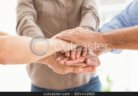 Business colleagues stacking hands together stock photo, Close up of business colleagues stacking hands together at office by Wavebreak Media
