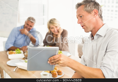 Casual business people looking at tablet while lunch stock photo, Casual business people looking at tablet while lunch in the office by Wavebreak Media