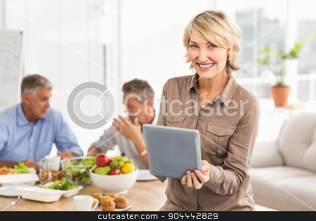 Smiling casual businesswoman using tablet at lunch stock photo, Portrait of smiling casual businesswoman using tablet at lunch in the office by Wavebreak Media