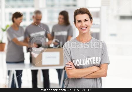 Smiling female volunteer with arms crossed stock photo, Portrait of smiling female volunteer with arms crossed in the office by Wavebreak Media