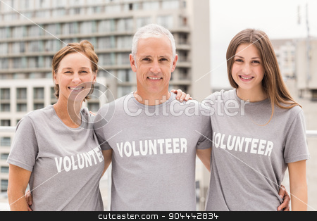 Smiling volunteers putting arms around each other stock photo, Portrait of smiling volunteers putting arms around each other on roof of building by Wavebreak Media