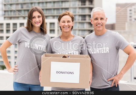 Smiling volunteers holding donation box stock photo, Portrait of smiling volunteers holding donation box on roof of building by Wavebreak Media