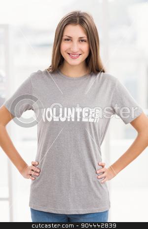 Smiling brunette volunteer with hands on hips stock photo, Portrait of smiling brunette volunteer with hands on hips in the office by Wavebreak Media