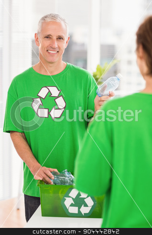Smiling eco-minded man holding recycling bottle stock photo, Portrait of smiling eco-minded man holding recycling bottle in the office by Wavebreak Media