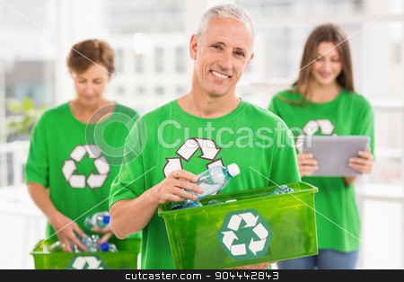Smiling eco-minded man holding recycling box stock photo, Portrait of smiling eco-minded man holding recycling box in the office by Wavebreak Media