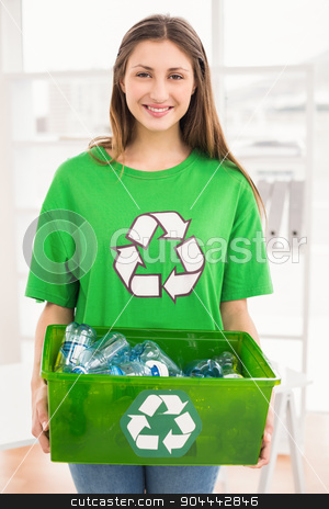 Smiling eco-minded brunette holding recycling box stock photo, Portrait of smiling eco-minded brunette holding recycling box in the office by Wavebreak Media