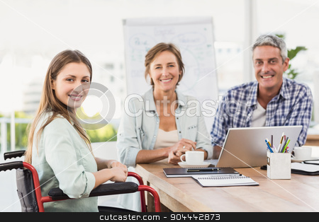 Casual businesswoman in wheelchair with colleagues stock photo, Portrait of casual businesswoman in wheelchair with colleagues in the office by Wavebreak Media