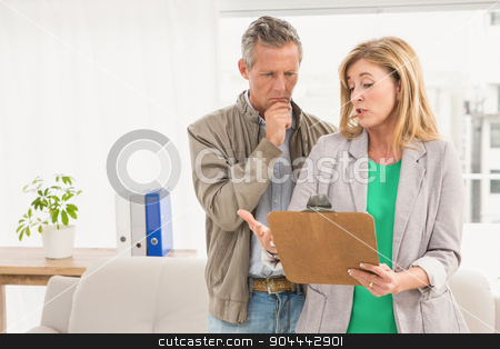 Casual business colleagues looking at clipboard  stock photo, Casual business colleagues looking at clipboard in the office by Wavebreak Media