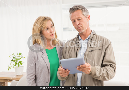 Casual business colleagues working with tablet stock photo, Casual business colleagues working with tablet in the office by Wavebreak Media