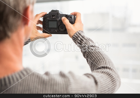 Rear view of man taking pictures with camera stock photo, Rear view of man taking pictures with camera in the office by Wavebreak Media