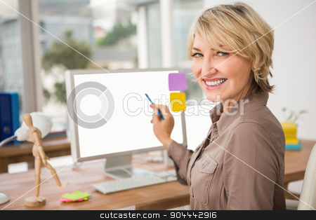Smiling casual designer pointing blank computer screen stock photo, Portrait of smiling casual designer pointing blank computer screen in the office by Wavebreak Media