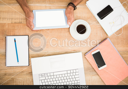 Hands holding tablet next to several devices stock photo, Hands holding tablet next to several devices on wooden desk by Wavebreak Media