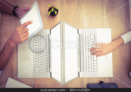 Casual business colleagues using several devices stock photo, Casual business colleagues using several devices on wooden desk by Wavebreak Media