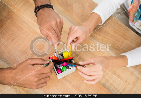 Casual business colleagues sorting pens stock photo, Casual business colleagues sorting pens on wooden desk by Wavebreak Media