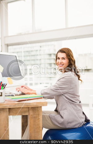 Casual businesswoman sitting on exercise ball while working stock photo, Portrait of casual businesswoman sitting on exercise ball while working in the office by Wavebreak Media