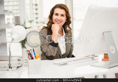 Smiling casual businesswoman working at desk stock photo, Portrait of smiling casual businesswoman working at desk in the office by Wavebreak Media