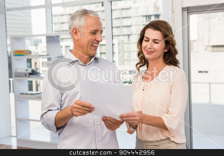 Casual business colleagues looking at documents stock photo, Casual business colleagues looking at documents in the office by Wavebreak Media