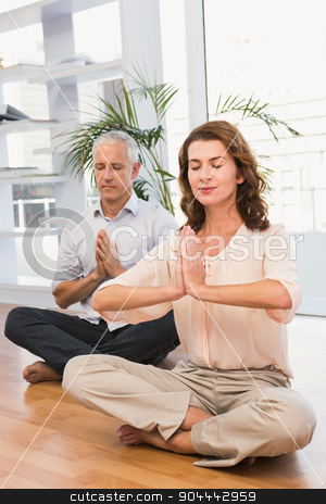 Peaceful casual business colleagues meditating stock photo, Peaceful casual business colleagues meditating in the office by Wavebreak Media