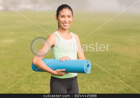 Smiling sporty woman holding exercise mat stock photo, Portrait of smiling sporty woman holding exercise mat in parkland by Wavebreak Media