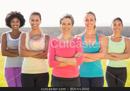 Smiling sporty women with arms crossed stock photo, Portrait of smiling sporty women with arms crossed in parkland by Wavebreak Media