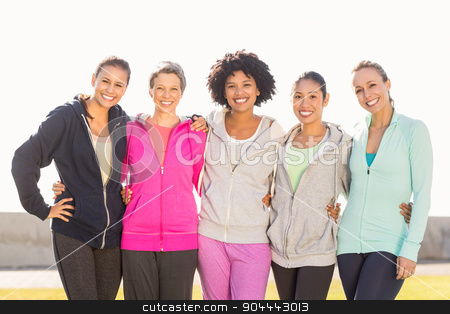 Smiling sporty women with arms around each other stock photo, Portrait of smiling sporty women with arms around each other in parkland by Wavebreak Media