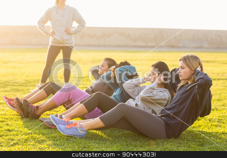 Sporty women doing sit ups during fitness class stock photo, Sporty women doing sit ups during fitness class in parkland by Wavebreak Media