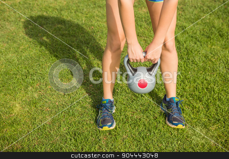 Sporty woman exercising with kettlebell  stock photo, Sporty woman exercising with kettlebell in parkland by Wavebreak Media