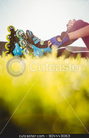 Woman wearing inline skates sitting in grass stock photo, Woman wearing inline skates sitting in grass at promenade by Wavebreak Media