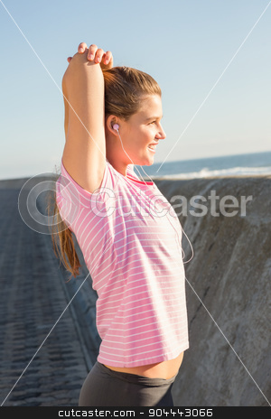 Smiling sporty blonde stretching and listening to music stock photo, Smiling sporty blonde stretching and listening to music at promenade by Wavebreak Media