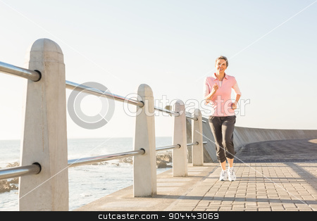 Smiling sporty woman jogging at promenade stock photo, Smiling sporty woman jogging at promenade on a sunny day by Wavebreak Media