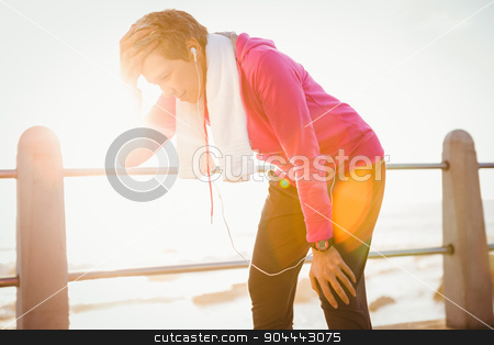 Tired sporty woman listening to music and resting stock photo, Tired sporty woman listening to music and resting at promenade by Wavebreak Media