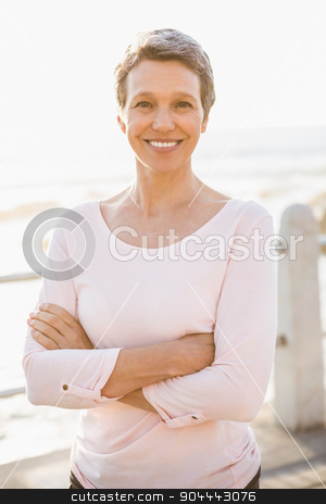 Smiling sporty woman with arms crossed at promenade stock photo, Portrait of smiling sporty woman with arms crossed at promenade on a sunny day by Wavebreak Media