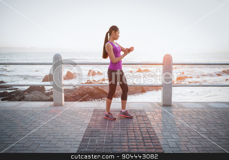Fit woman checking smart watch at promenade stock photo, Fit woman checking smart watch at promenade on a sunny day by Wavebreak Media