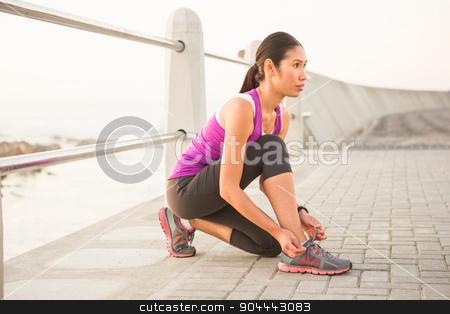 Fit woman tying shoelace at promenade stock photo, Fit woman tying shoelace at promenade on a sunny day by Wavebreak Media
