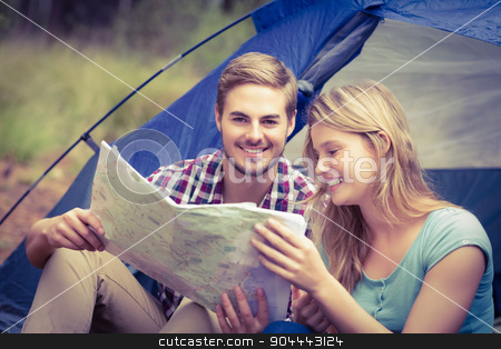 Young pretty hiker couple sitting in a tent looking at map stock photo, Young pretty hiker couple sitting in a tent looking at map in the nature by Wavebreak Media