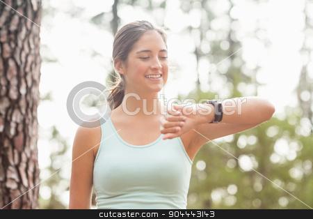 Happy jogger looking at watch stock photo, Happy jogger looking at watch in the nature by Wavebreak Media