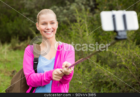 Smiling female hiker taking a selfie stock photo, Smiling female hiker taking a selfie with a selfie stick in the nature by Wavebreak Media