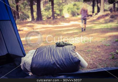 Sleeping bag in front of blonde camper walking away stock photo, Sleeping bag in front of blonde camper walking away in the nature by Wavebreak Media