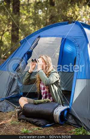 Blonde camper looking through binoculars stock photo, Blonde camper looking through binoculars while sitting in tent by Wavebreak Media