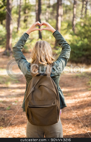 Rear view of blonde hiker framing heart with hands stock photo, Rear view of blonde hiker framing heart with hands in the nature by Wavebreak Media