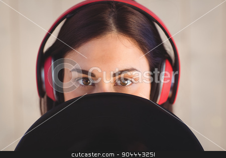 Pretty hipster listening to music holding vinyl stock photo, Pretty hipster listening to music holding vinyl on wooden planks background by Wavebreak Media