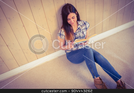 Pretty hipster reading blue book stock photo, Pretty hipster reading blue book on wooden planks background by Wavebreak Media
