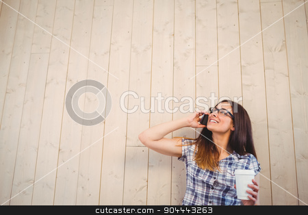 Pretty hipster on the phone holding cup stock photo, Pretty hipster on the phone holding cup on wooden planks background by Wavebreak Media