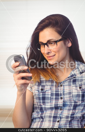 Pretty hipster using her phone stock photo, Pretty hipster using her phone in a bright room by Wavebreak Media