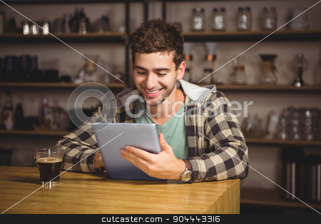 Smiling hipster having coffee and using tablet computer stock photo, Smiling hipster having coffee and using tablet computer at coffee shop by Wavebreak Media
