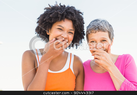 Two sporty women laughing to camera stock photo, Portrait of two sporty women laughing to camera at promenade by Wavebreak Media