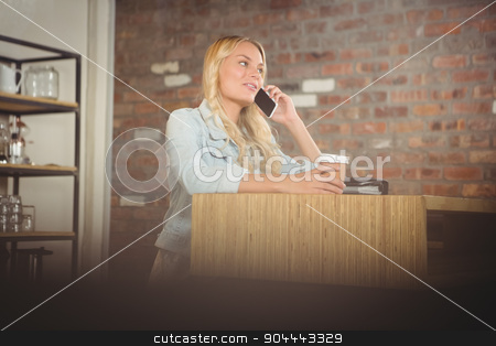 Pretty blonde phoning and holding take-away cup stock photo, Pretty blonde phoning and holding take-away cup at coffee shop by Wavebreak Media