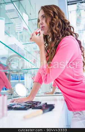 Pretty woman trying a lipstick stock photo, Pretty woman trying a lipstick at the pharmacy by Wavebreak Media