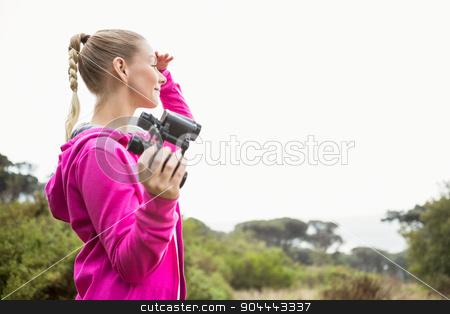 Female hiker looking away and holding binoculars stock photo, Female hiker looking away and holding binoculars in the nature by Wavebreak Media