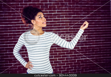 Young woman gesturing  stock photo, Young woman gesturing against a red brick wall by Wavebreak Media